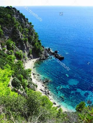Вид на синее море с зеленым холмом