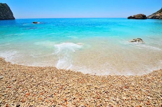 Пляж и мелких камушек с голубой водой